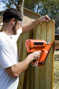 28065930 - man wearing safety glasses uses a portable nail gun to attach wood pickets to the rail as he builds a privacy fence in the backyard.
