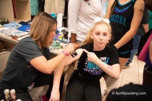 Autumn applying a sparkle breast cancer ribbon to Excel Cheerleader.