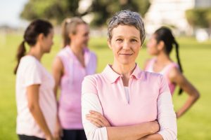44523821 - portrait of woman wearing pink for breast cancer in front of friends in parkland