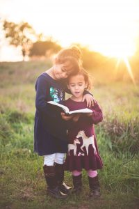 girl reading to her sister